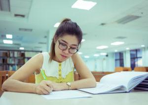 Student in library. (Sutichak/Shutterstock)